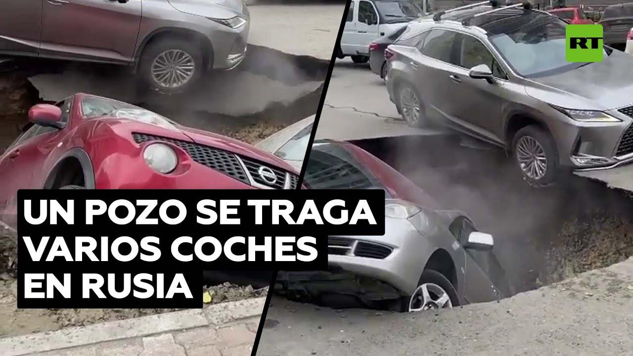 Autos estacionados caen en un sovacón que se abrió en una calle de Novosibirsk