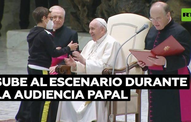 Un niño sube al escenario y consigue sentarse junto a Francisco y una gorra papal de regalo